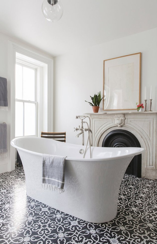 freestanding bathtub in the center of master bathroom with fireplace