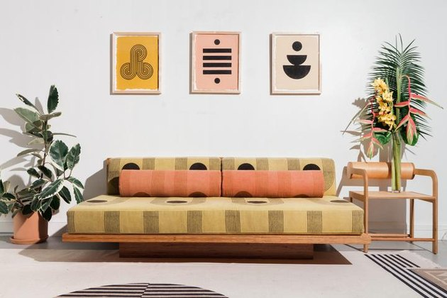 living room with striped couch and three framed geometric prints on the wall
