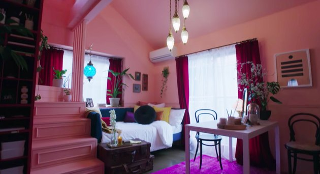 pink room with pink steps and a chandelier