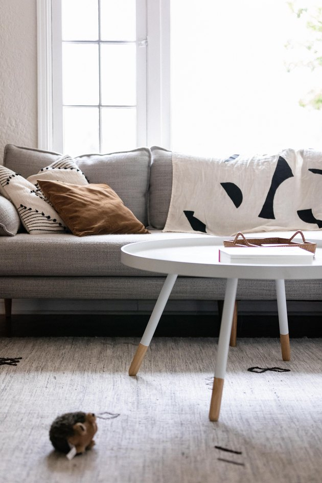 white coffee table in front of gray sofa in living room space