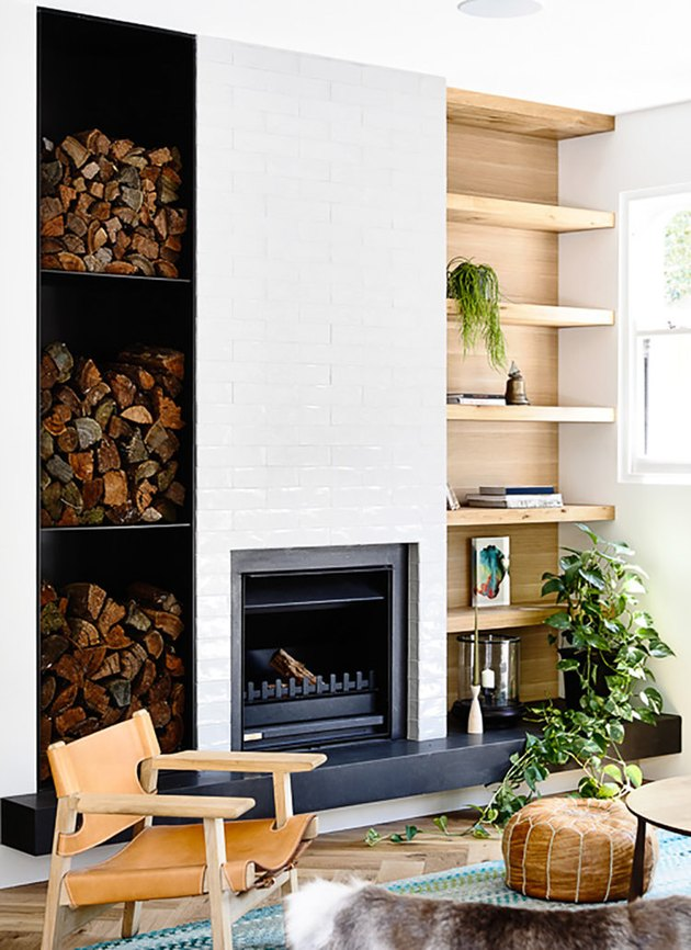 midcentury fireplace with built in shelving and stacked wood