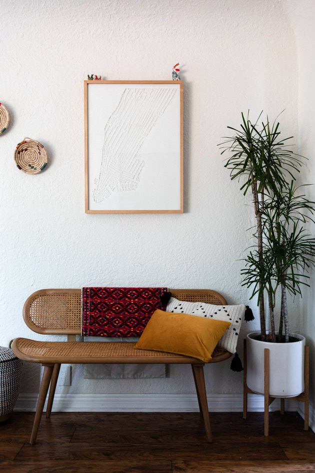 bench with pillows and framed artwork nearby