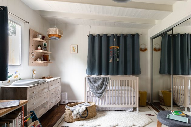 nursery space with wooden dresser, crib and dark blue curtain