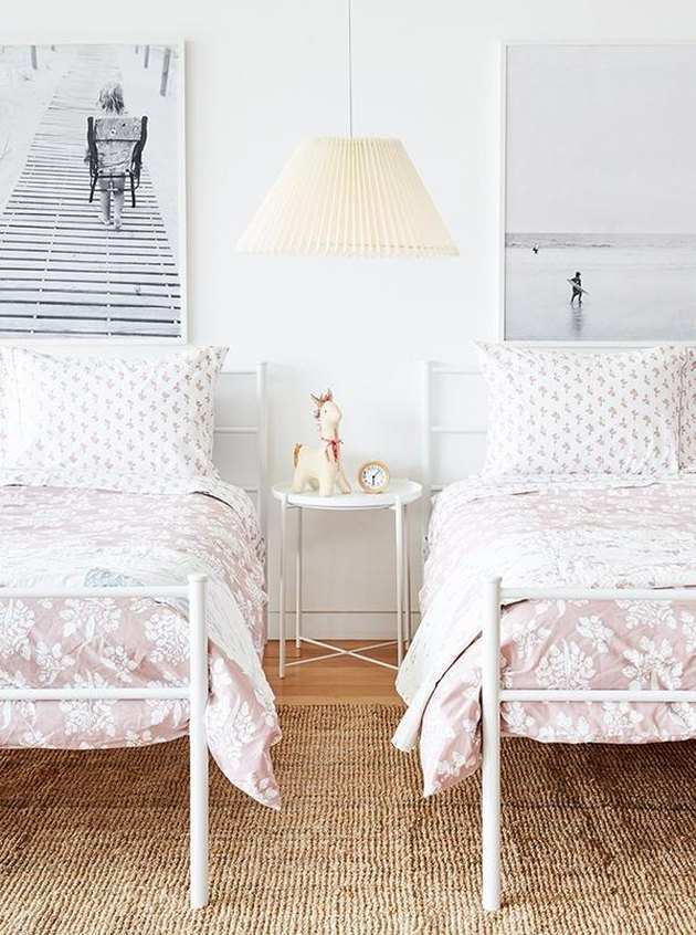 pink bedding in pink kids bedroom idea with black and white photographs and jute rug