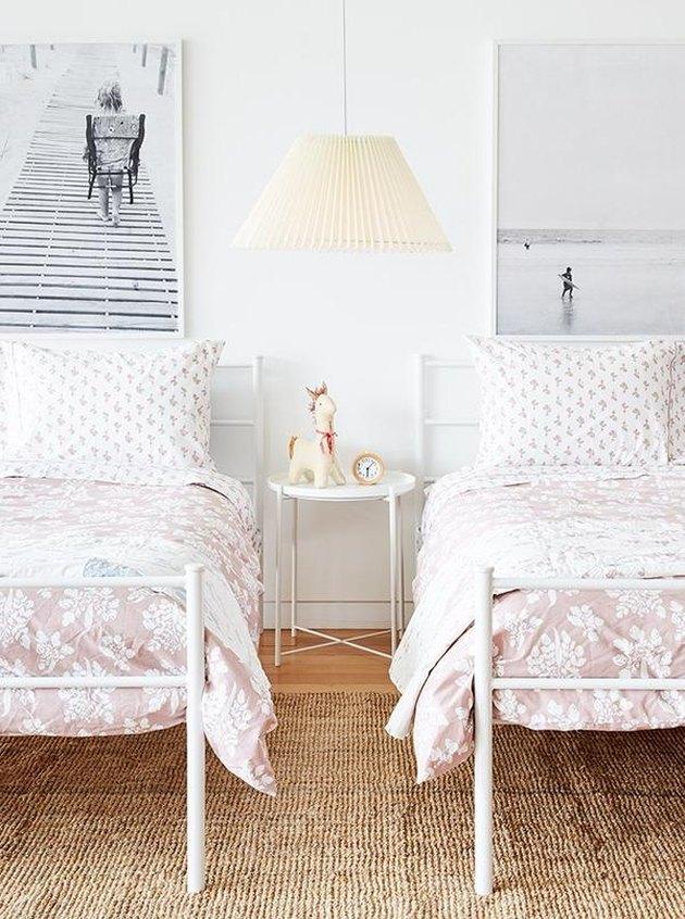 розовое постельное белье в розовой детской спальне с черно-белыми фотографиями и джутовым ковриком
