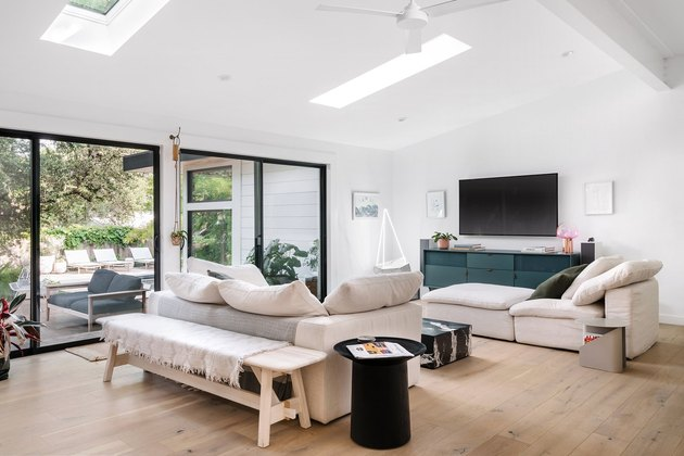 white living room with floor to ceiling windows and sofas