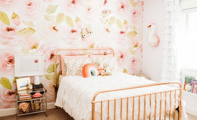 copper bed in pink kids bedroom idea with floral wallpaper and ruffled drapery