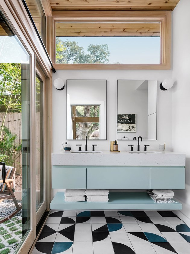 Bathroom with blue vanity and geometric tile