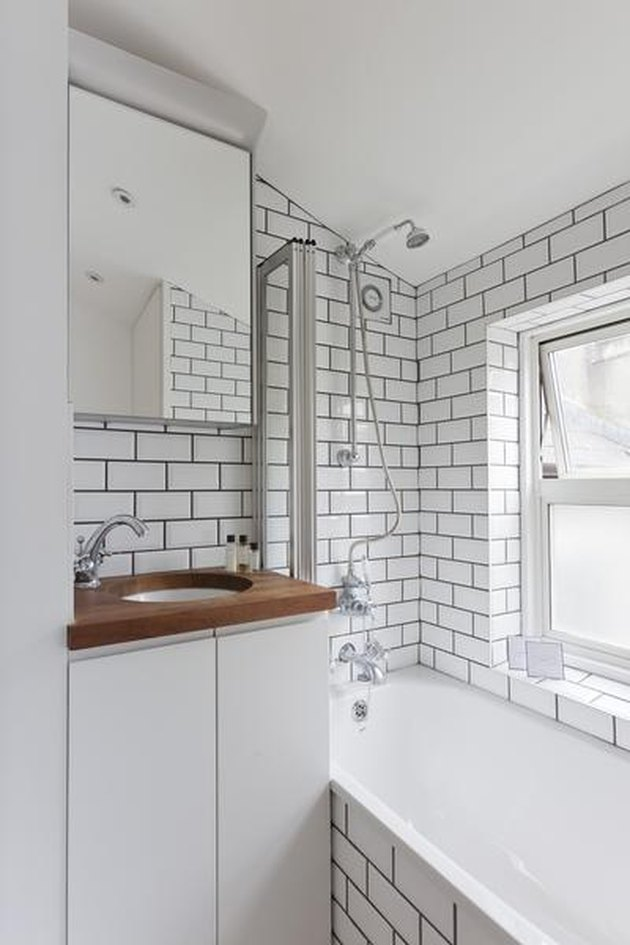 small white bathroom with subway tile walls and wood countertop