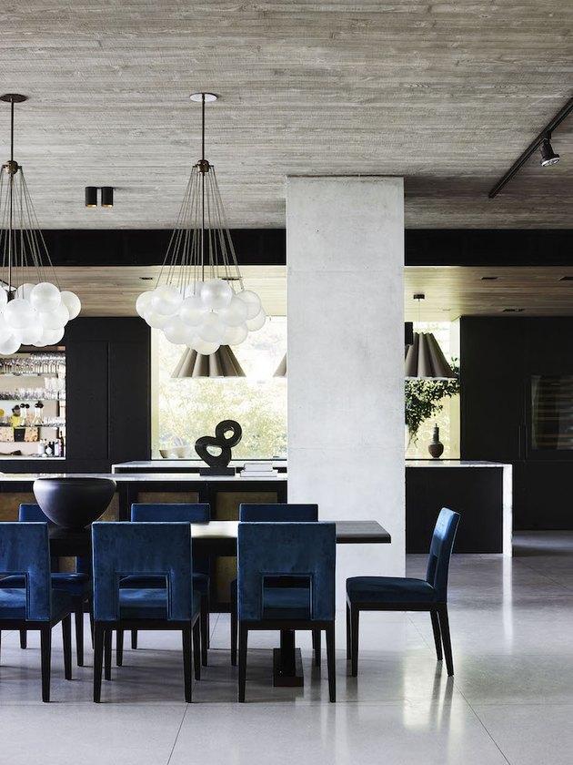 concrete kitchen flooring in modern kitchen with blue velvet dining chairs