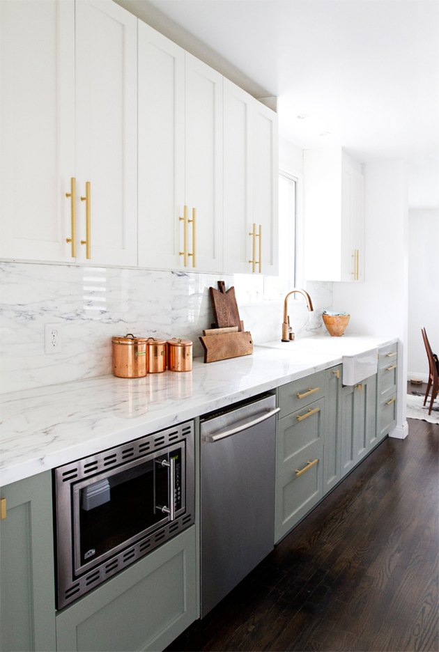 two-tone kitchen cabinets with white and light green and brass pulls