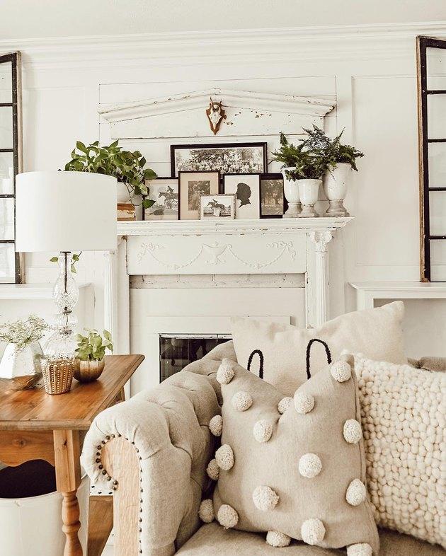 all white farmhouse mantel decorating idea in the living room with tufted sofa