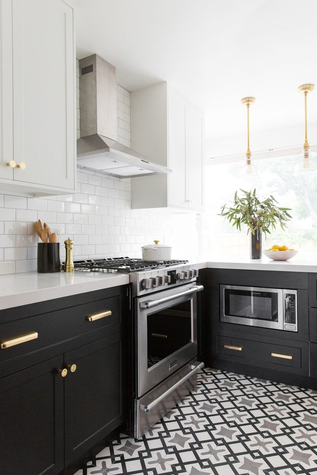 two-tone kitchen cabinets with black and white and brass hardware