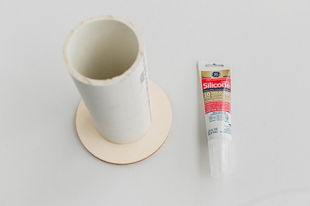 Attach the cut PVC pipe to the circles using silicone caulk.