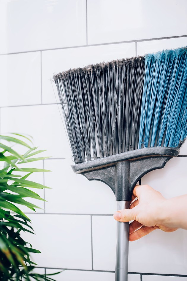 hand reaching for broom against white tiled wall