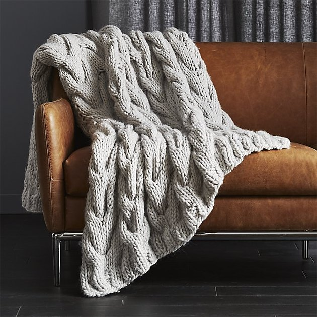 gray blanket on leather sofa