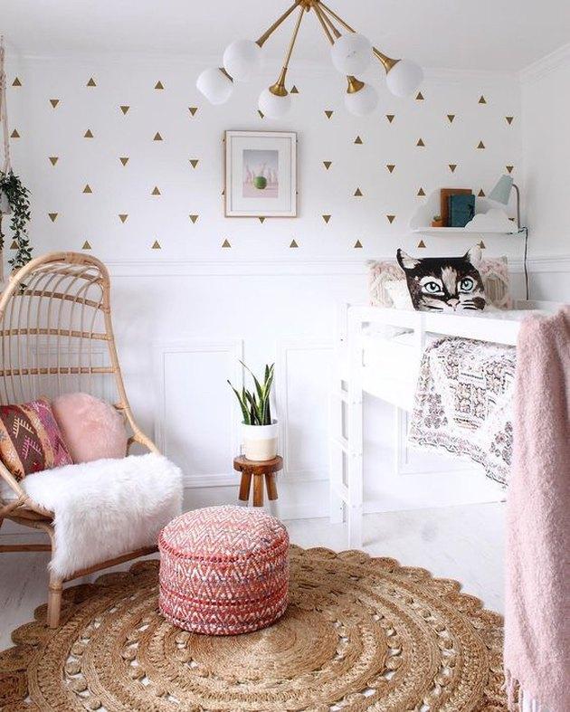Розовая детская спальня с люстрой середины века и стулом из ротанга