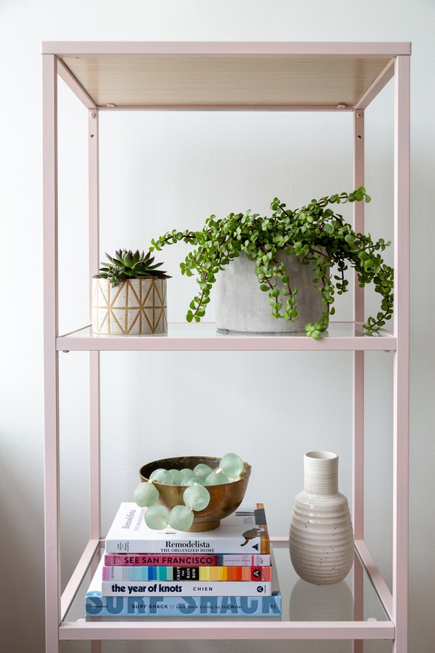 Pink metal shelf with books and plants and a white vase.