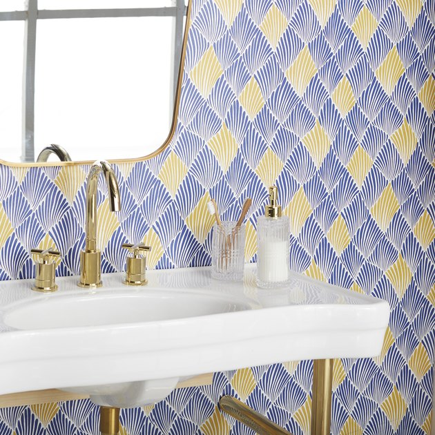 bathroom sink with blue and gold wallpaper