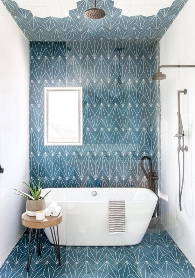 Shower and tub combo in this bathroom designed by Andrea West Design, with blue concrete tile on the floor and wall.