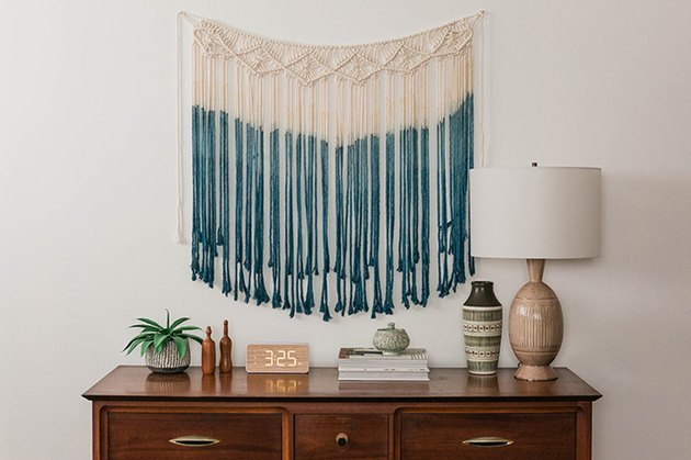 White and blue macrame art hanging on wall.