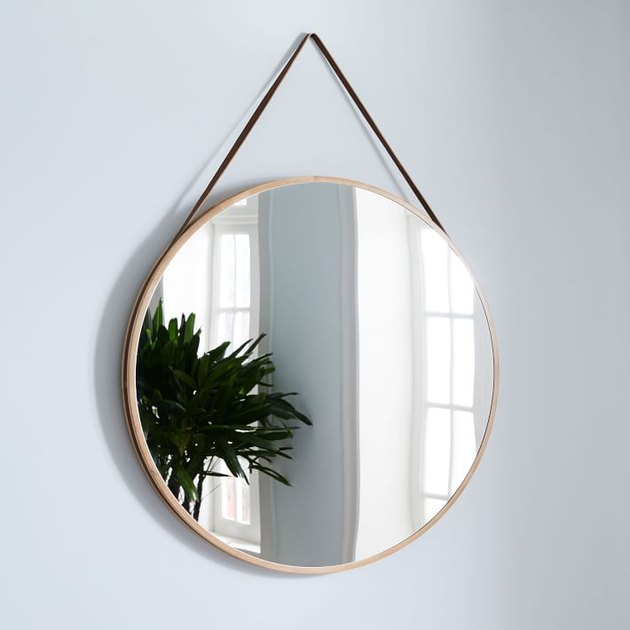Large circular mirror hung by leather strap