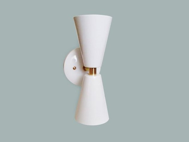 White two-cone sconce shaped loosely like upside-down bow tie with white base and gold details
