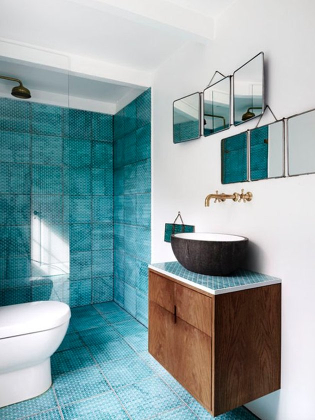 Blue tile on the floor and wall of this master bathroom with modern sink.