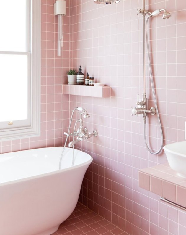 Pink square tile in shower with white bath tub.
