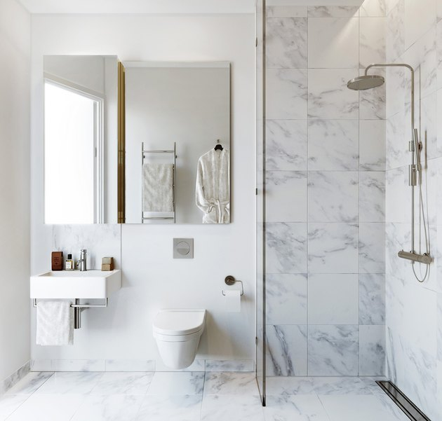 white bathroom with marble shower and flooring