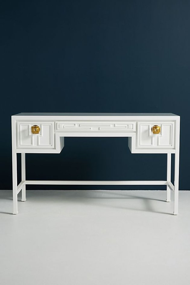 White desk with three drawers. Side drawers feature lucite knob with gold base