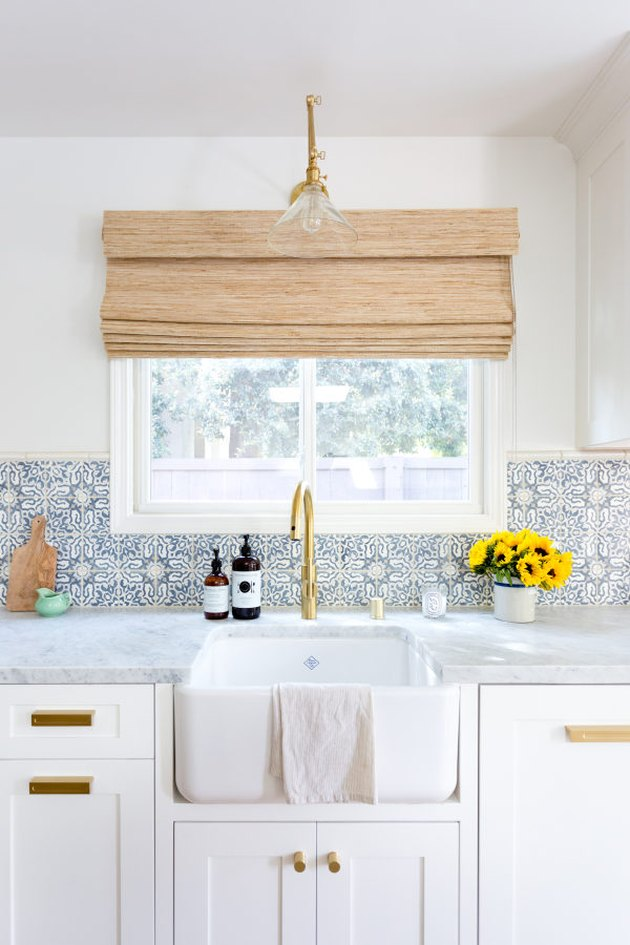 Blue and white Moroccan tile backsplash with apron front sink and white cabinets