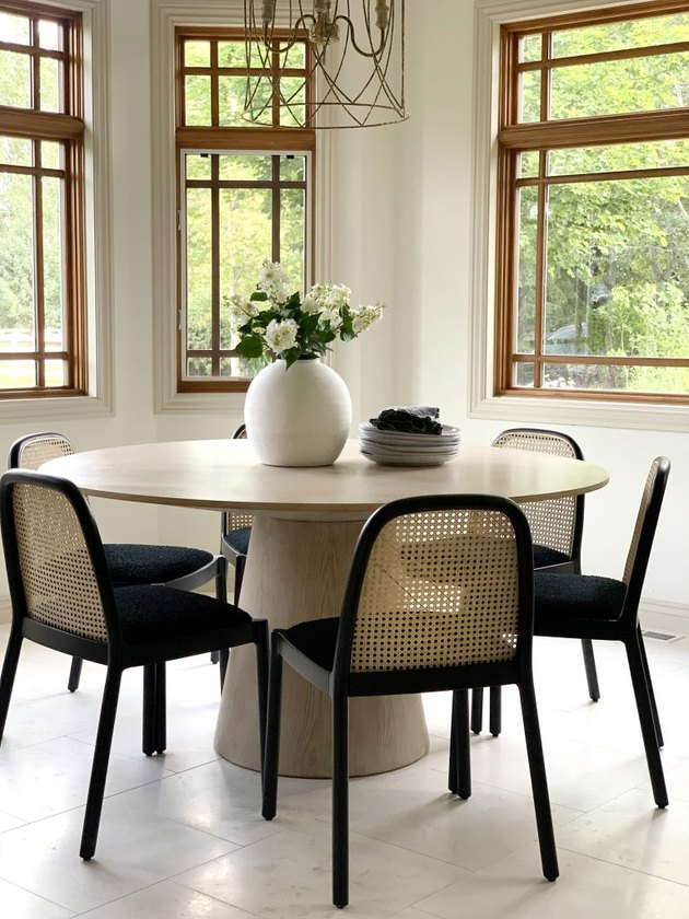 minimal dining room table centerpiece with round table and cane chairs