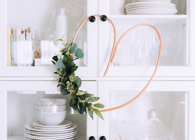 Copper pipe heart wreath hanging on glass kitchen cabinet.