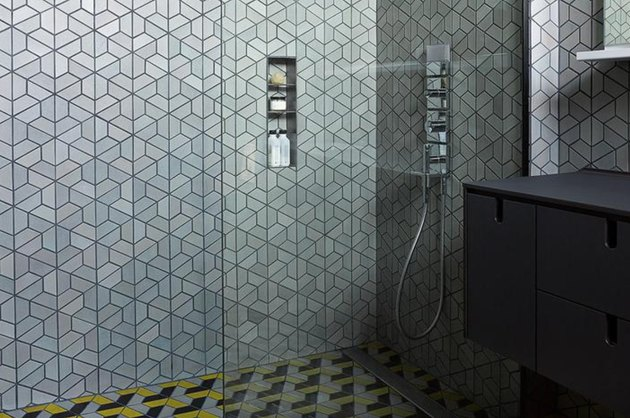 Hexagon tiling in master shower with gunmetal, black, and yellow colors.