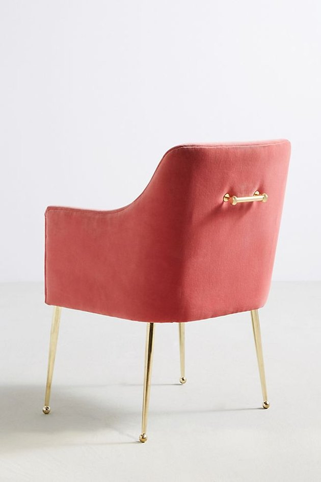 Modern coral velvet armchair with brass legs and brass handle on back