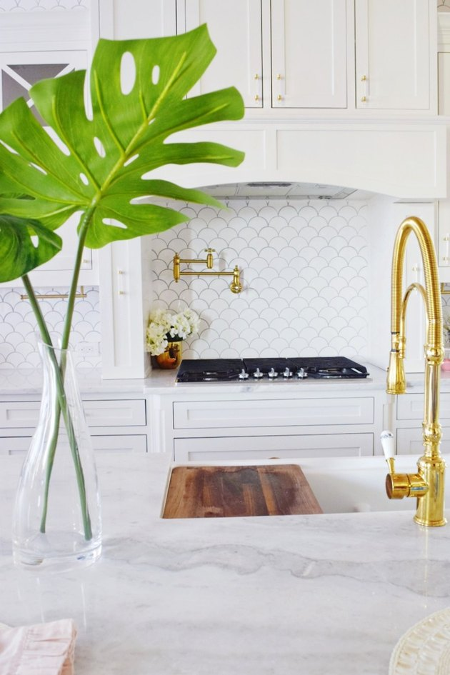 White fish scale Moroccan tile backsplash with marble countertop and white cabinets
