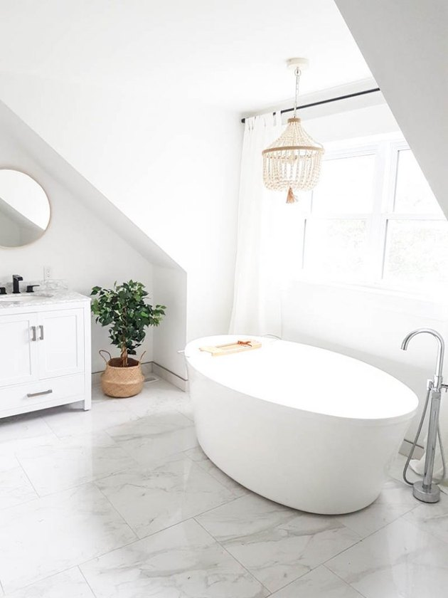 white bathroom with marble flooring and freestanding tub