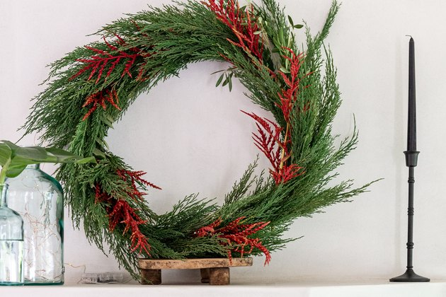 Faux holiday wreath with cedar on mantel.