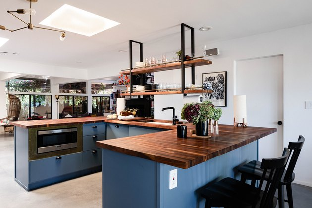 open concept kitchen with blue kitchen island and concrete flooring