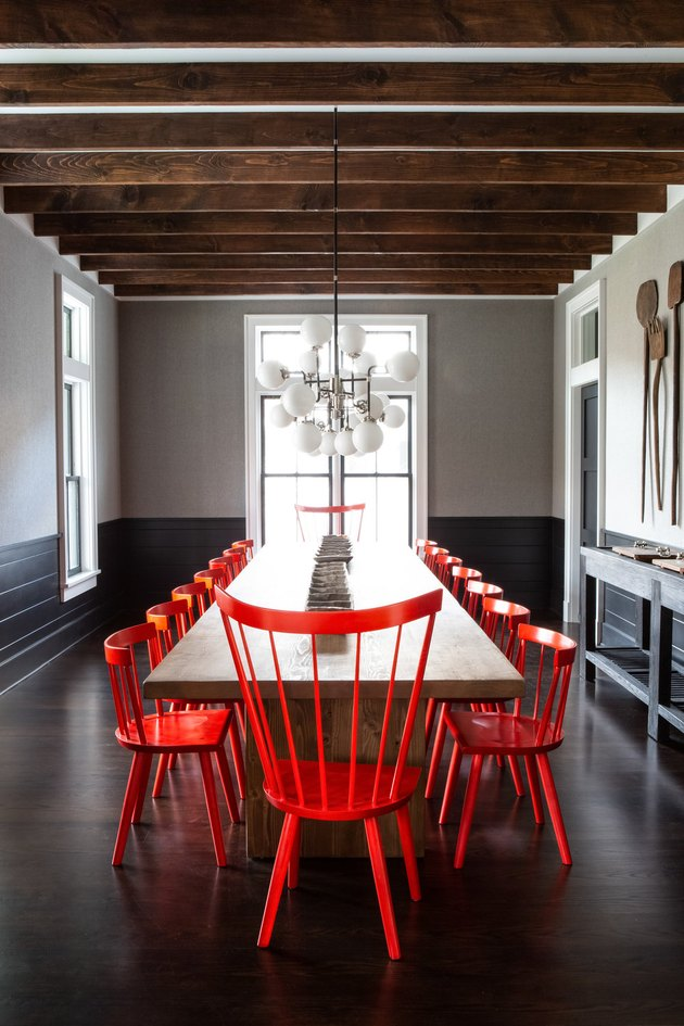 black dining room wainscoting with red chairs and wood beams by Chango & Co.