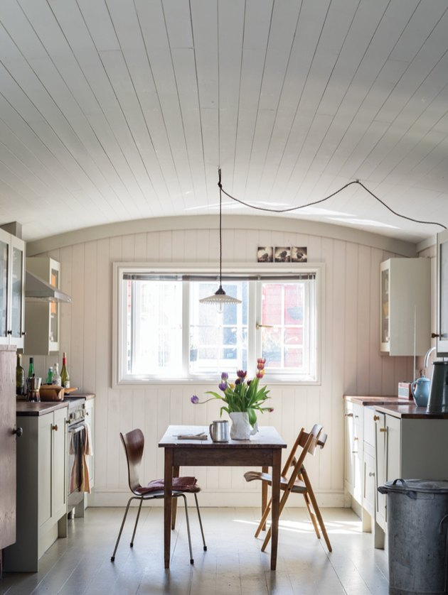 Kitchen with arched ceiling, pendant light, and dining table and chairs in middle