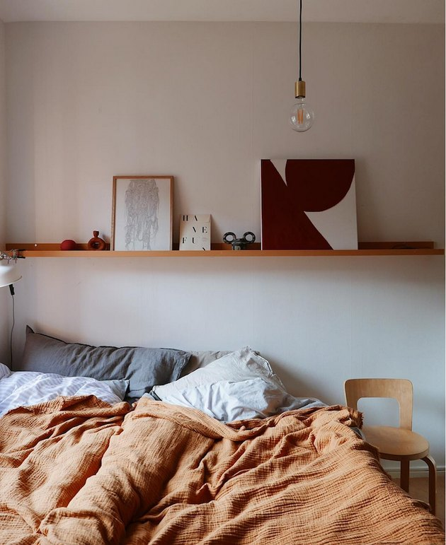 bedroom with orange blanket and warm wood accents