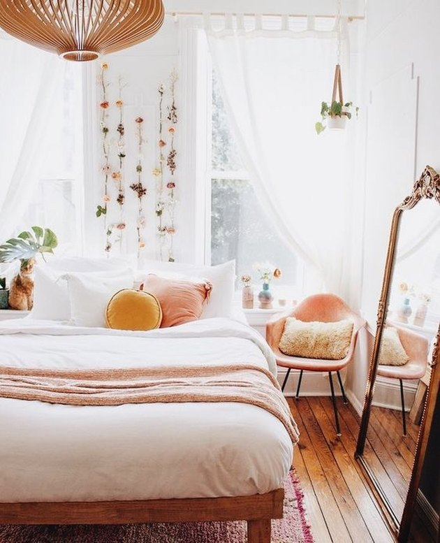bedroom with peach accents and flowers hanging on the wall