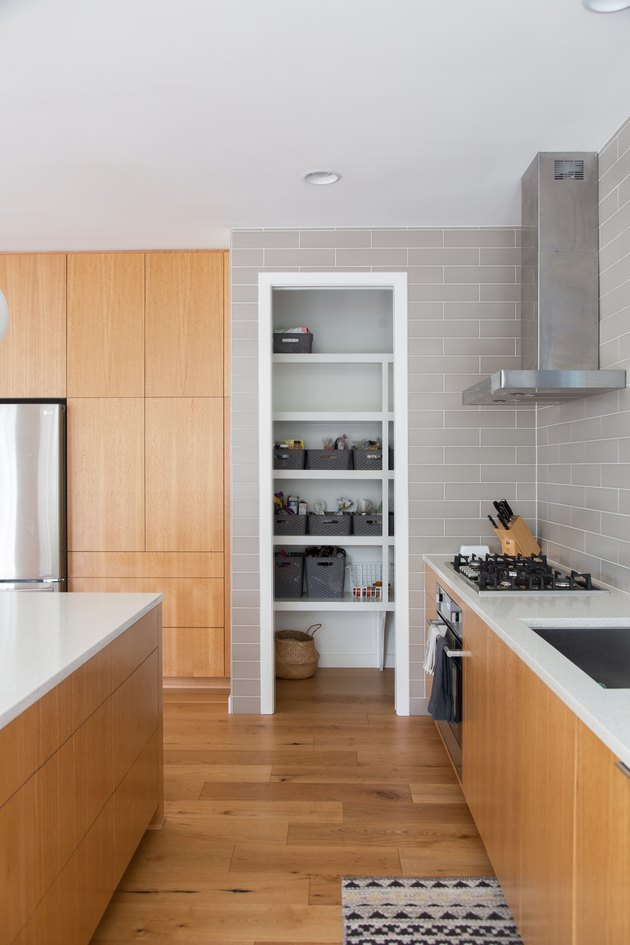galley style kitchen with view of industrial kitchen vent and hardwood floors