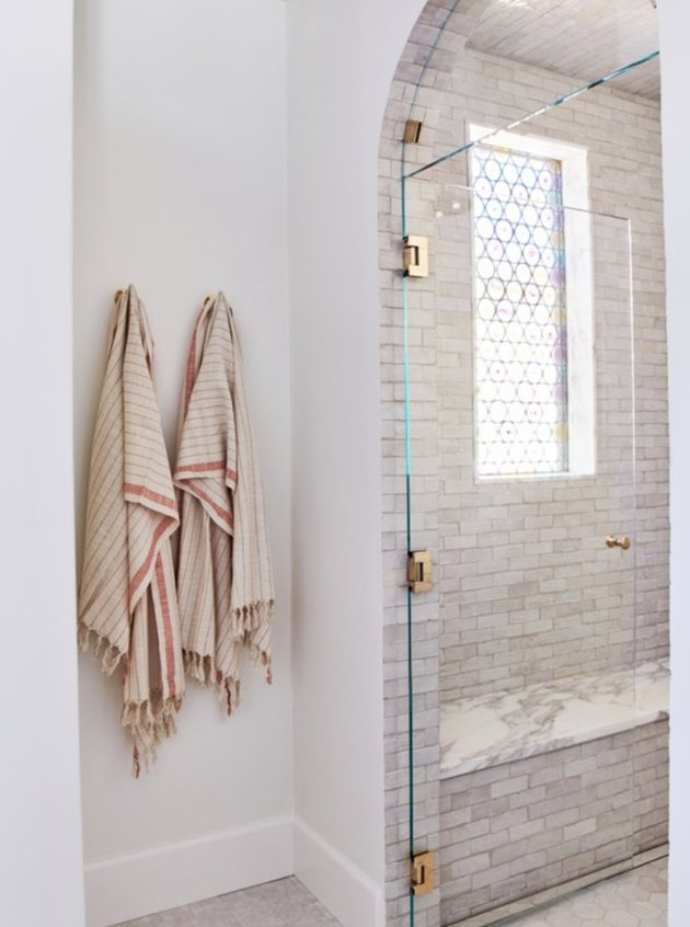 An alcove shower with frameless door shows off it's tile work.
