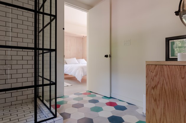 view of bedroom from the bathroom with colorful floor tiles