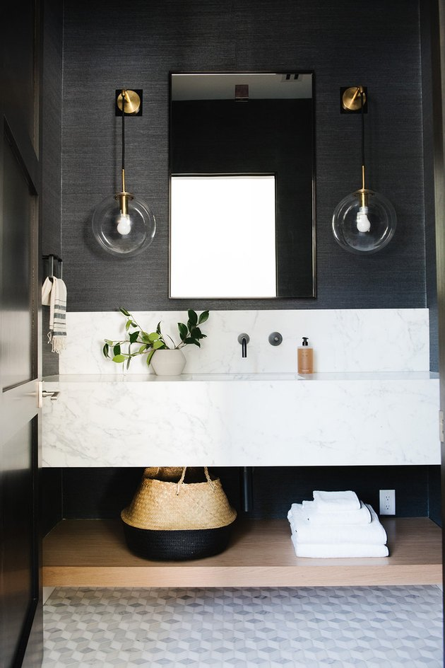 black bathroom with marble vanity and marble mosaic floor tile