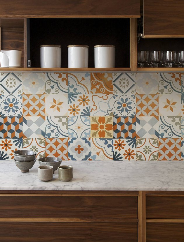 Orange, blue, and white Mexican tile backsplash in varying patterns with wood cabinetry