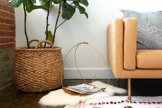 Leather and gold hoop magazine rack on sheepskin rug next to basket planter and plant.